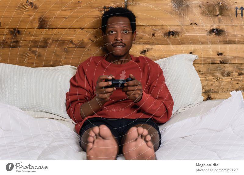 Mann hat Spaß beim Spielen von Spielen Lifestyle Freude Glück schön Freizeit & Hobby Haus Schlafzimmer Entertainment Erfolg Kind Technik & Technologie Mensch