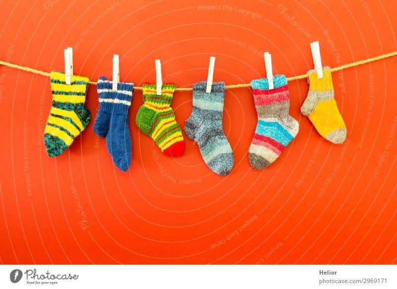 Bunte Socken an einer Wäscheleine auf rotem Hintergrund Stil Design Winter Mode frisch retro Wärme weich blau mehrfarbig grün weiß fleißig Reinlichkeit