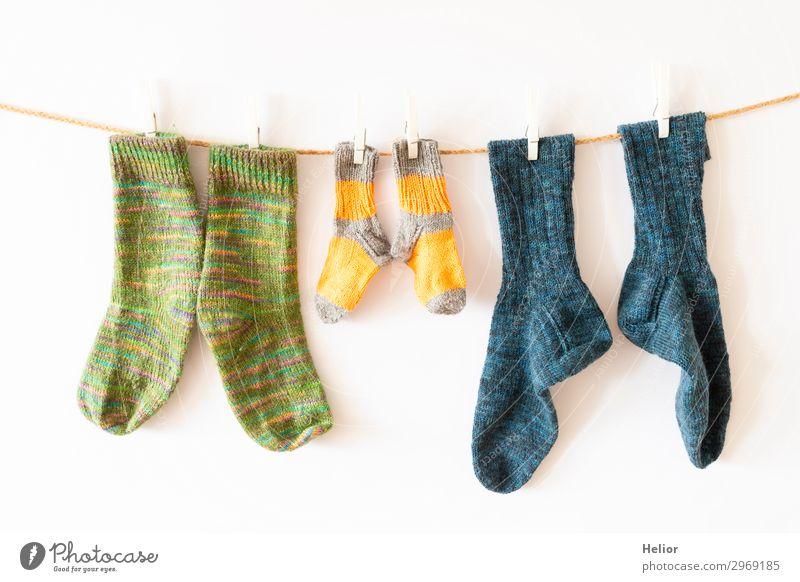 Bunte Socken an einer Wäscheleine auf weissem Hintergrund Stil Design Handarbeit stricken Winter Mode frisch retro Wärme weich blau gelb grün weiß Ordnungsliebe