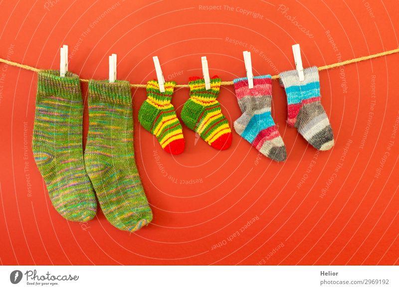 Bunte Socken an einer Wäscheleine auf rotem Hintergrund Stil Design Handarbeit stricken Winter Mode frisch retro trocken Wärme weich blau mehrfarbig grün