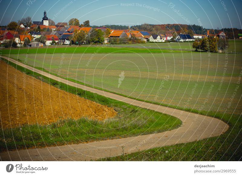 Mein Weg der geschwungen durch eine Wiese geteilt , zu einer Kleinstadt in Franken führt. Im Hintergrund das Dorf, Häuser und die Kirche. Freude Leben