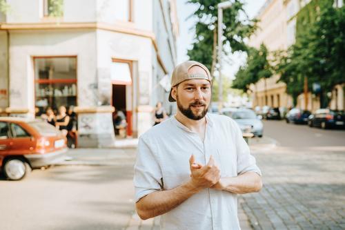 Mann mit Basecap auf der Straße stehend attraktiv Baseball Vollbart bärtig Verschlussdeckel lässig Kaukasier heiter Stadtleben selbstbewusst cool Emotion