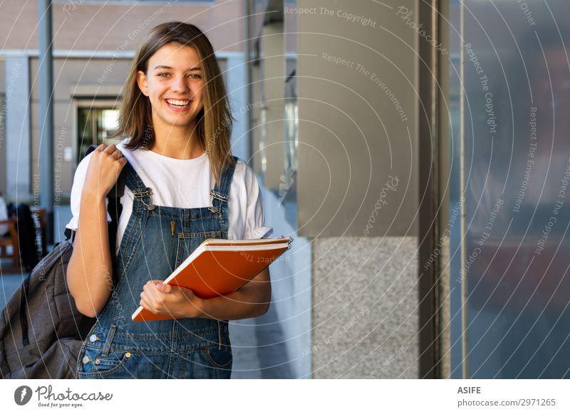 Lächelndes Schülermädchen am Schuleingang Lifestyle Glück schön Studium Frau Erwachsene Jugendliche brünett lachen stehen niedlich Teenager Mädchen Kaukasier