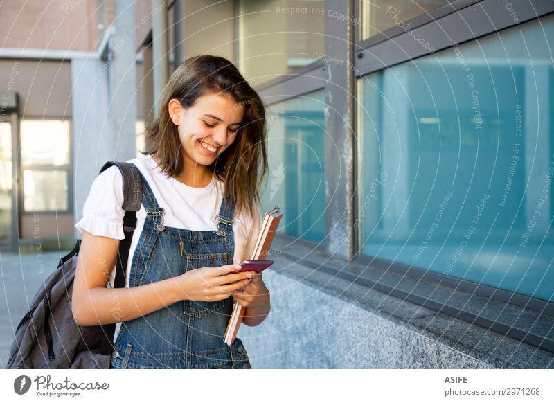Glückliche Schülerin benutzt Smartphone auf dem Schulkorridor Lifestyle schön Schule Studium Telefon PDA Technik & Technologie Frau Erwachsene Jugendliche