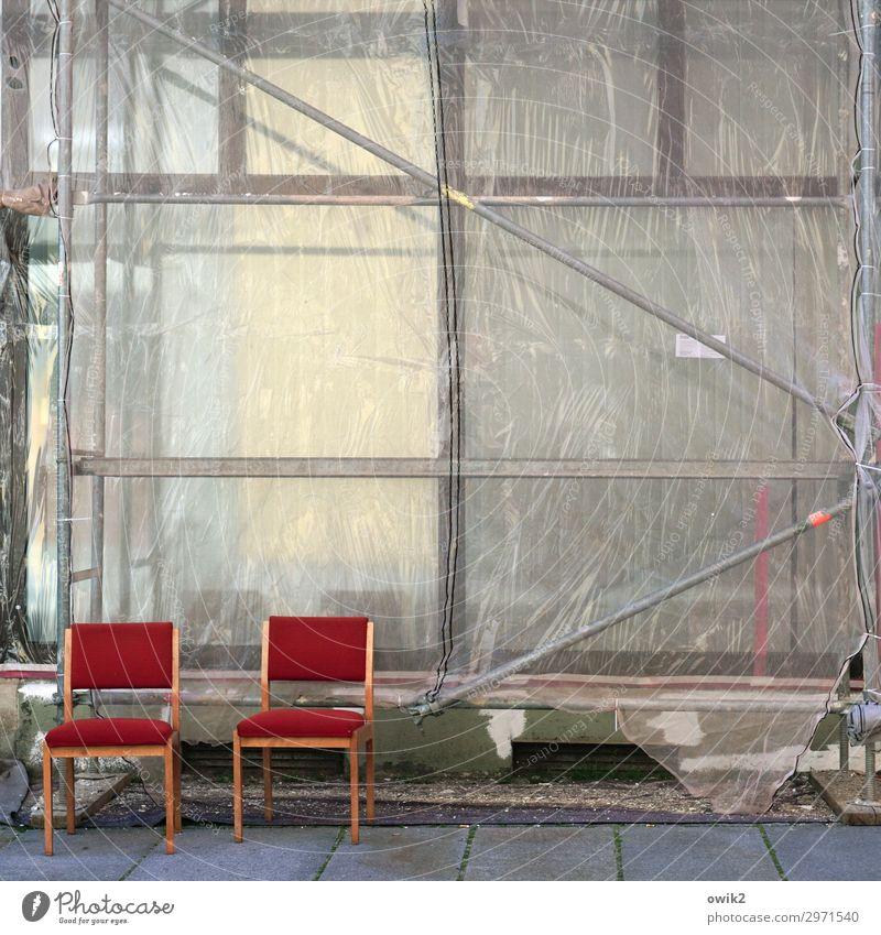 Draußen sitzen Haus Gebäude Baustelle Bürgersteig Stuhl paarweise Zusammensein rot leuchtende Farben geduldig Pause Baugerüst Abdeckung Kunststoff Metall Holz