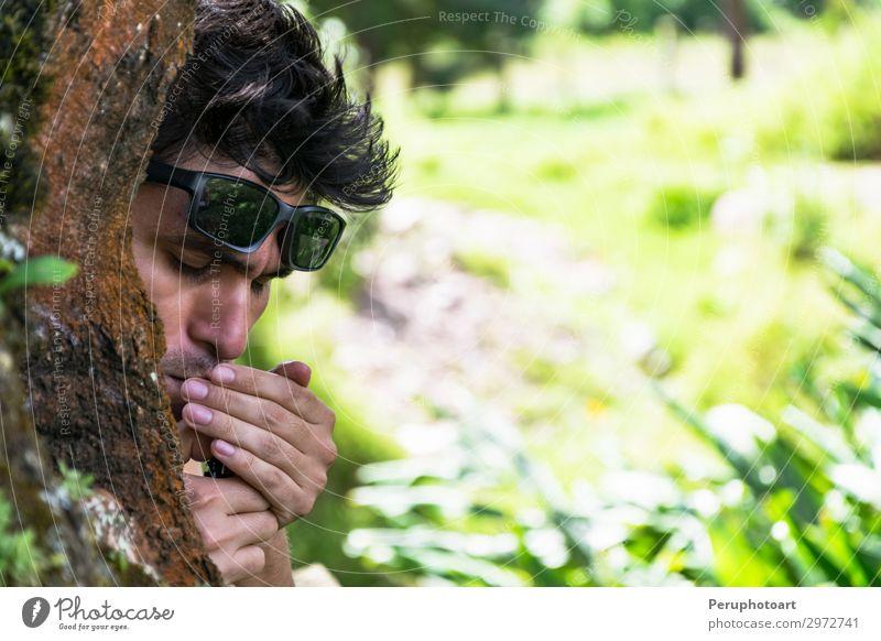 Junger Mann, der eine Zigarre hinter einem Baum im Wald anzündet. Alkohol Lifestyle Reichtum Gesicht Erholung Mensch maskulin Erwachsene Park Sonnenbrille alt