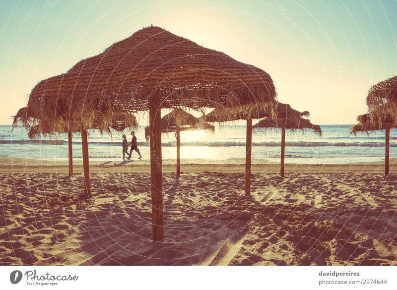Holzschirme an einem Strand bei Sonnenuntergang exotisch schön Erholung Freizeit & Hobby Ferien & Urlaub & Reisen Tourismus Sommer Meer Insel Natur Landschaft