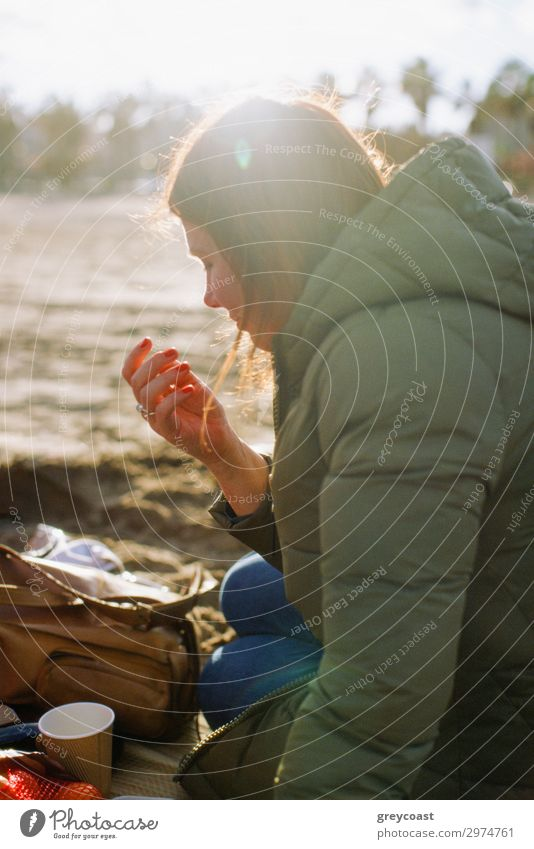 Ein Picknick am Straßenrand Freizeit & Hobby Mensch Junge Frau Jugendliche Erwachsene 1 30-45 Jahre Natur Herbst Park Mantel Lächeln sitzen Snack jung eine