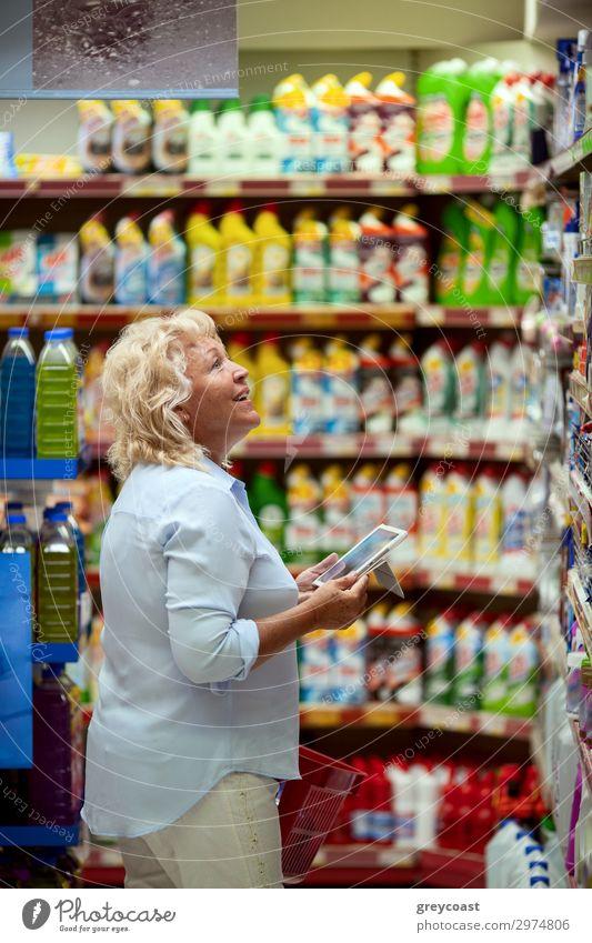 Eine lächelnde Frau mittleren Alters in einem hellblauen Hemd steht in einer Haushaltsabteilung eines Supermarktes. Sie hält ein Tablet und einen roten Einkaufskorb in ihren Händen. Eine Frau schaut sich die Regale an, auf der Suche nach etwas Bestimmtem