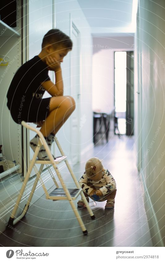 Ein kleines Mädchen studiert etwas auf den Hüften, während ihr älterer Bruder sie von oben auf der Treppe sitzend beobachtet Leben Freizeit & Hobby Spielen Kind
