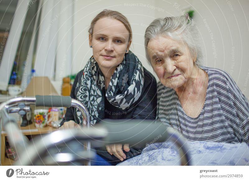 Ein Porträt einer jungen, blonden Frau, die dicht neben einer älteren Dame sitzt, deren Hand auf ihrem Arm liegt. Beide sind leicht lächelnd Mensch feminin