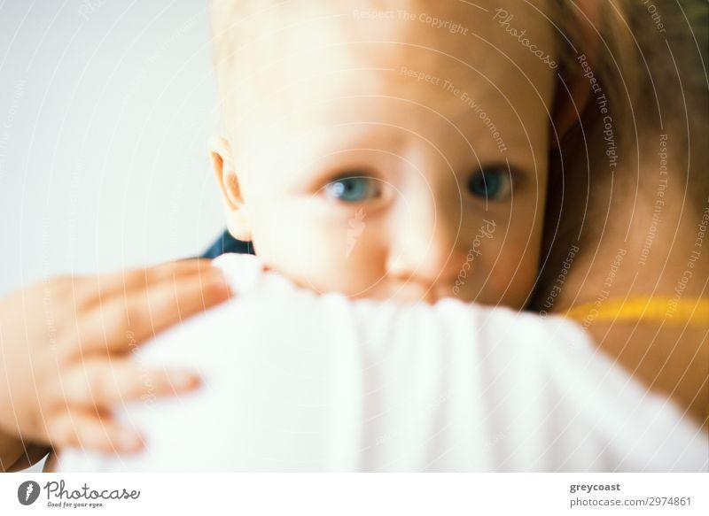 Ein unscharfes Porträt eines blauäugigen Babys, das seine Mutter umarmt, die es in den Armen hält Kind Mensch feminin Mädchen Junge Frau Jugendliche Erwachsene