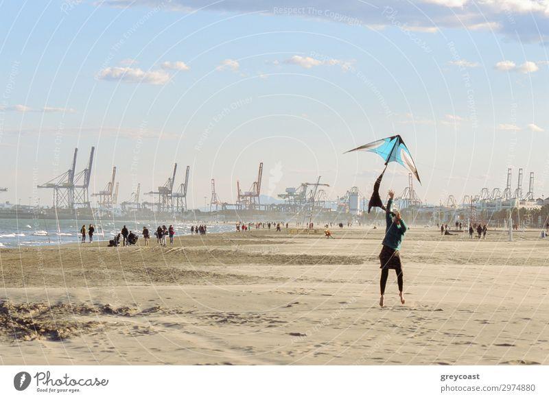 Eine Frau fliegt einen Drachen am Meeresufer. Promenierende Menschen und ein Hafen mit Kränen für Frachtschiffe im Hintergrund Freizeit & Hobby Strand Winter
