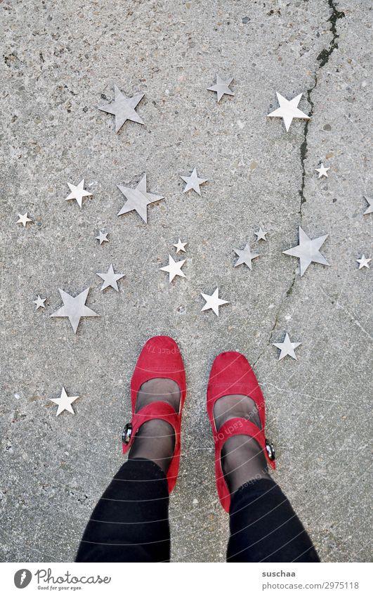 frau, die auf der straße steht und nach unten in die sterne schaut Beine Füße weiblich Frau stehen Damenschuhe Schuhe rot seltsam skurril Straße Asphalt Riss