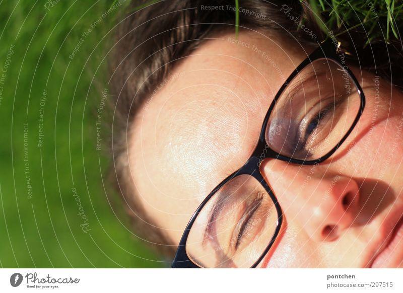Gesicht einer Frau mit Brille im Gras. Augen halb geschlossen. Blinzeln im Sonnenlicht. Erholen und entspannen feminin Junge Frau Jugendliche Erwachsene Kopf
