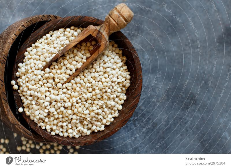 Rohweißes Sorghumkorn Gemüse Vegetarische Ernährung Diät Schalen & Schüsseln Löffel natürlich grau Korn Müsli roh Textfreiraum Samen rustikal Holz