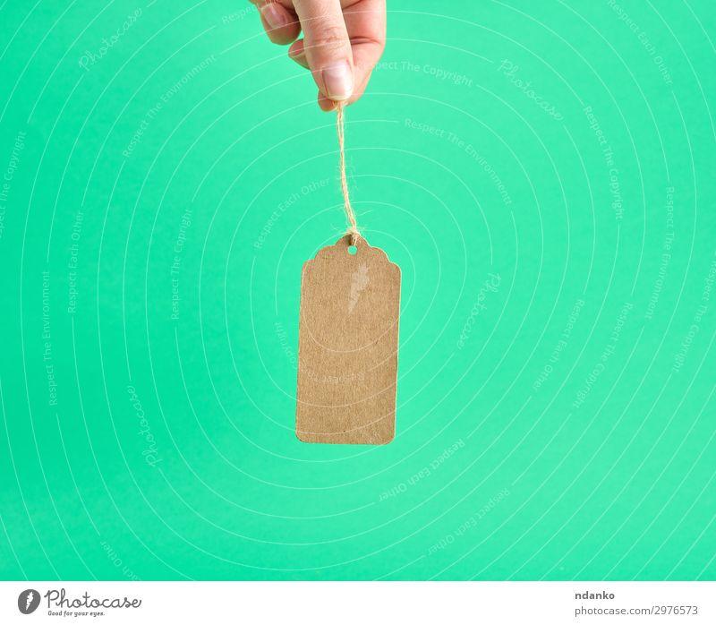 weibliche Hand hält ein papierbraunes leeres Etikett. Körper Business Seil Mensch Frau Erwachsene Finger Papier alt hängen verkaufen klein retro gelb grün weiß