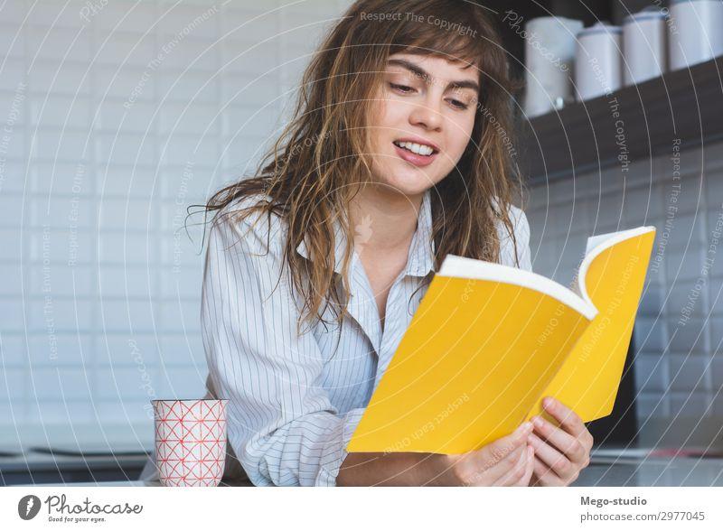 Frau, die ein Buch liest Frühstück Lifestyle Freude Glück schön Erholung lesen Haus Tisch Küche Mensch Erwachsene Denken Lächeln sitzen modern weiß Einsamkeit