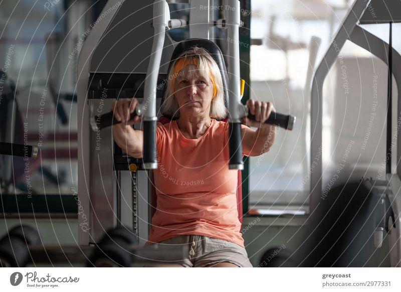 Eine ältere Frau übt Übungen auf einem Fitnesstrainer Sport Sport-Training Sportstätten Mensch feminin Erwachsene 1 45-60 Jahre blond schaukeln Senior Kaukasier