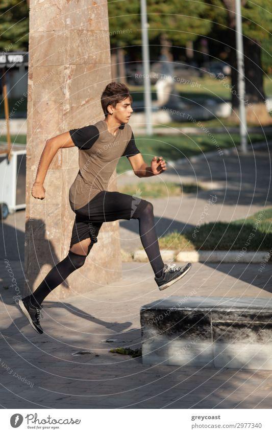 Ein Teenager macht Parkour in einem Stadtpark Sport Leichtathletik Joggen Mensch maskulin Junger Mann Jugendliche 1 13-18 Jahre T-Shirt Turnschuh schwarzhaarig