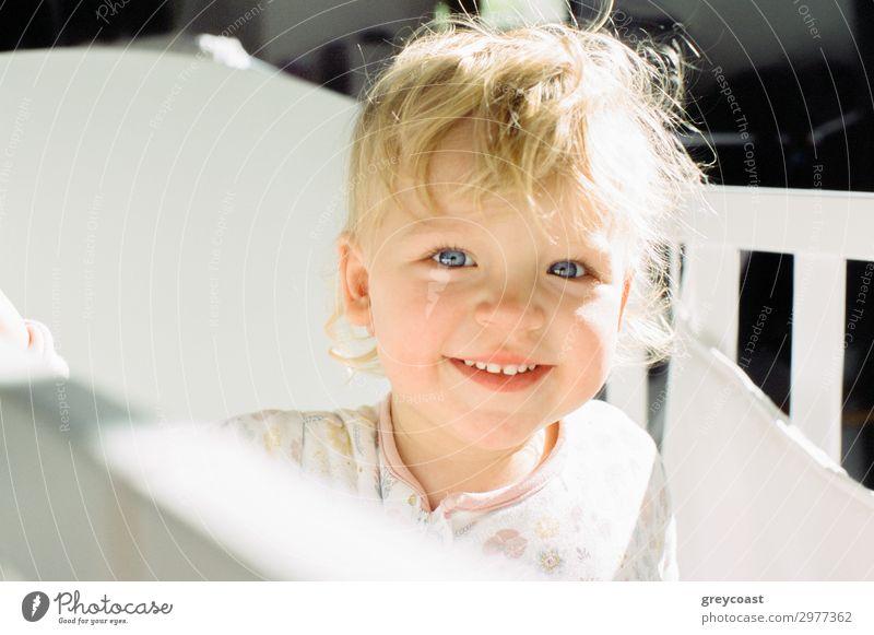 Porträt eines lächelnden Baby-Mädchens in ihrem Kinderbett Freude Bett Mensch feminin Kindheit 1 0-12 Monate blond Lächeln Fröhlichkeit kleines Mädchen Tochter