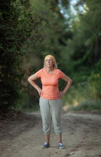 Eine Frau mittleren Alters steht auf einem Parkweg, die Hände in die Hüften gestemmt, müde von einer Joggingrunde Sport Mensch feminin Erwachsene