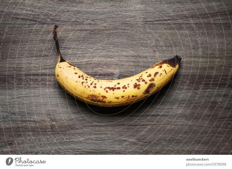 überreife Banana auf rustikalem Holzhintergrund Lebensmittel Frucht Ernährung Vegetarische Ernährung Gesunde Ernährung alt braun gelb Snack Banane Fleck