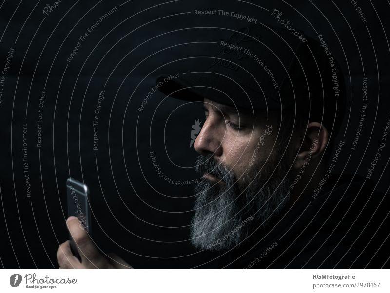 bearded man looking down at his mobile device Lifestyle kaufen Wirtschaft Börse Geldinstitut Telekommunikation Callcenter Business Erfolg sprechen Handy