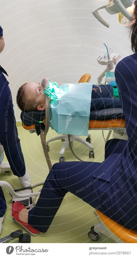 Ein Fragment eines Zahnarztzimmers mit einem Kind, das auf einem Zahnarztstuhl liegt, und einem Teil der Figur des Arztes Behandlung Arbeit & Erwerbstätigkeit