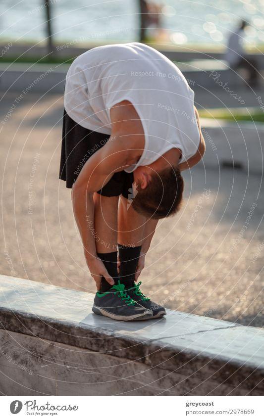 Ein Jugendlicher streckt sich, zieht den Kopf auf die Knie, im Freien Sport Leichtathletik Sportler Yoga maskulin Junger Mann 1 Mensch 13-18 Jahre T-Shirt