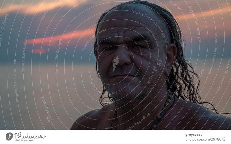 Ein Porträt eines Mannes mittleren Alters mit langen Haaren und ein paar Halsketten auf seiner nackten Brust Lifestyle Sommerurlaub maskulin Erwachsene