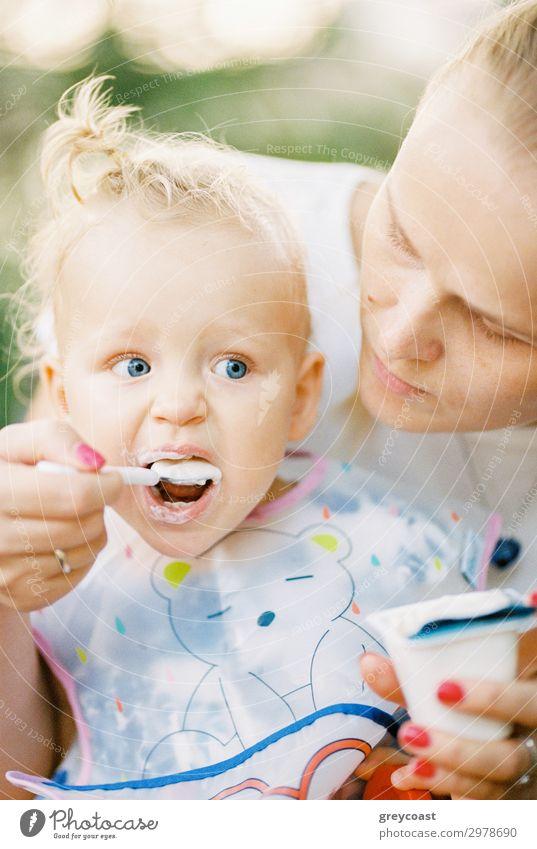 Ein kleines Mädchen wird von seiner Mutter mit Joghurt gefüttert Dessert Essen Löffel Kind Mensch feminin Baby Junge Frau Jugendliche Erwachsene