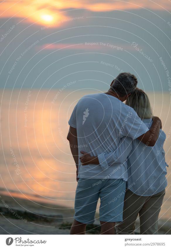 Ein Paar mittleren Alters, das sich umarmt und einen Sonnenuntergang am Meer beobachtet, wir sehen sie von hinten Ferien & Urlaub & Reisen Wellen Mensch