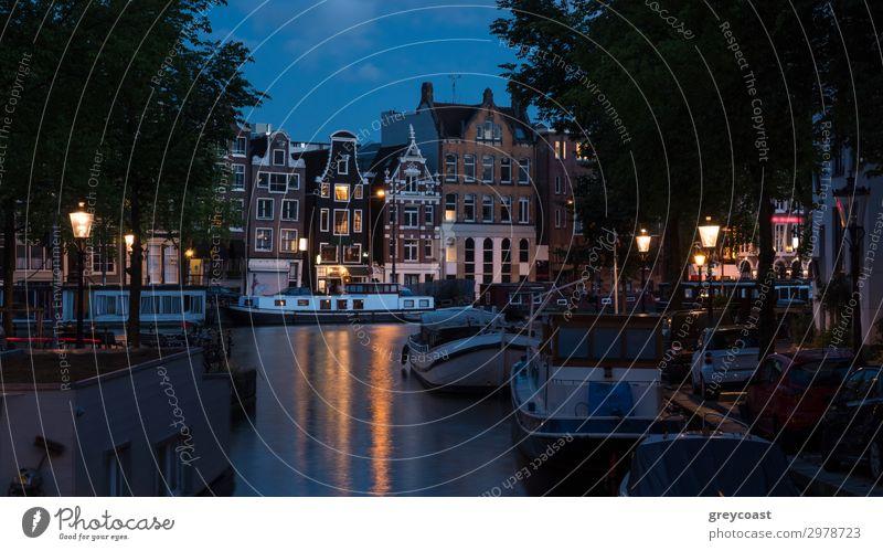 Amsterdamer Nachtszene mit traditionellen Häusern, an der Gracht vertäuten Booten und beleuchteten Laternen, Niederlande Ferien & Urlaub & Reisen Tourismus