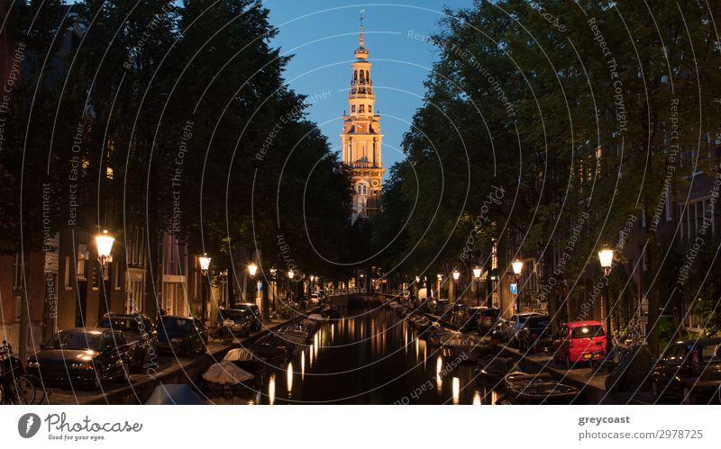 Amsterdamer Stadtbild bei Nacht. Szene mit Booten auf der mit Laternen gesäumten Gracht und Zuiderkerk, protestantische Kirche aus dem 17.