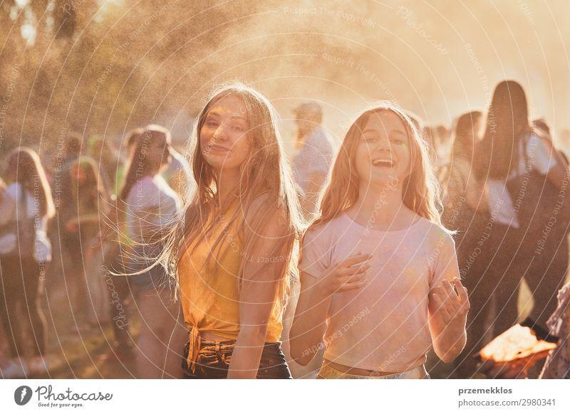 Porträt der glücklich lächelnden jungen Mädchen mit bunten Farben auf Gesichtern und Kleidung. Zwei Freunde verbringen Zeit auf holi Farbe Festival Lifestyle