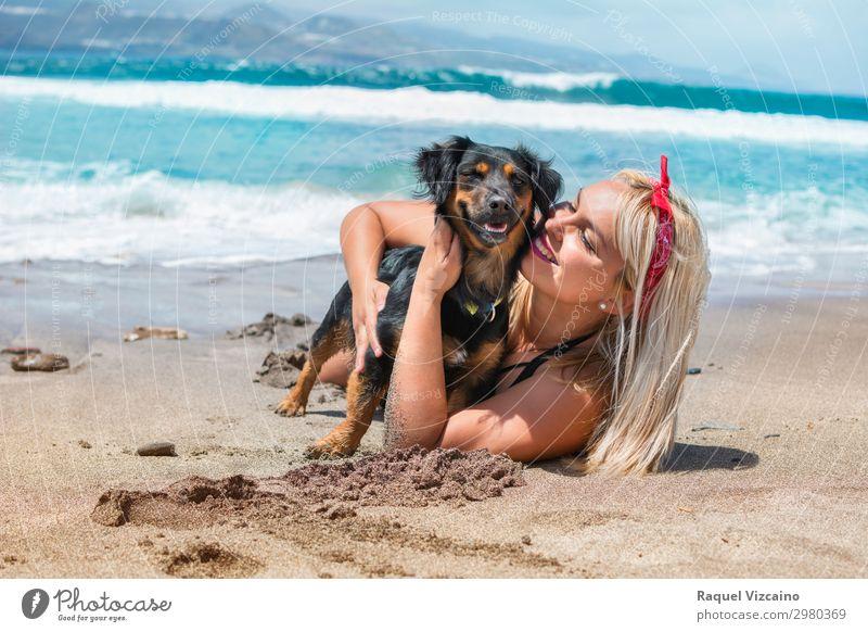 Frau, die ihren Hund am Strand umarmt. Lifestyle Wohlgefühl Ferien & Urlaub & Reisen Tourismus Sommer Sommerurlaub Sonnenbad Junge Frau Jugendliche Kopf Gesicht