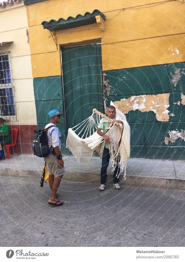Hammock merchant on columbian street Mensch maskulin Mann Erwachsene Leben 2 Gebäude Souvenir gelb grün Hängematte Händler Tourismus Kolumbien Reisefotografie
