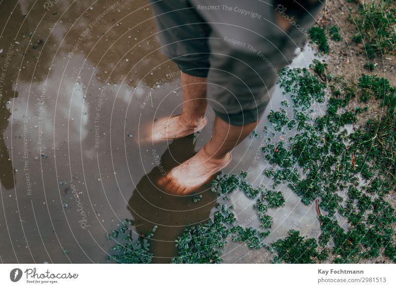 feet of a man standing inside a big puddle after a heavy rain Mensch Ferien & Urlaub & Reisen Natur Jugendliche Sommer Einsamkeit 18-30 Jahre Lifestyle Beine