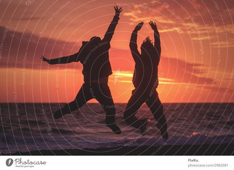 Paar springt am Strand im Sonnenuntergang strand sonnenuntergang abendrot Silhouette ferien urlaub küste nordsee wellen himmel erholung freude spaß tourismus