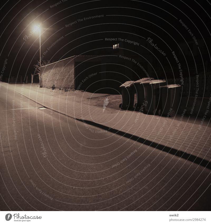 Am Hang Dorf Straße Bürgersteig Straßenbeleuchtung Laternenpfahl Müllbehälter Garage bedrohlich dunkel trist ruhig Dorfstraße friedlich geduldig Risiko Neigung