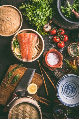 Authentische Zubereitung asiatischer Speisen mit Lachs, Gewürzen, Schüsseln und Stäbchen auf dunklem Küchentisch, Draufsicht. Verschiedene Zutaten, Utensilien und Werkzeuge auf dem Küchentisch.  Asiatische Küche