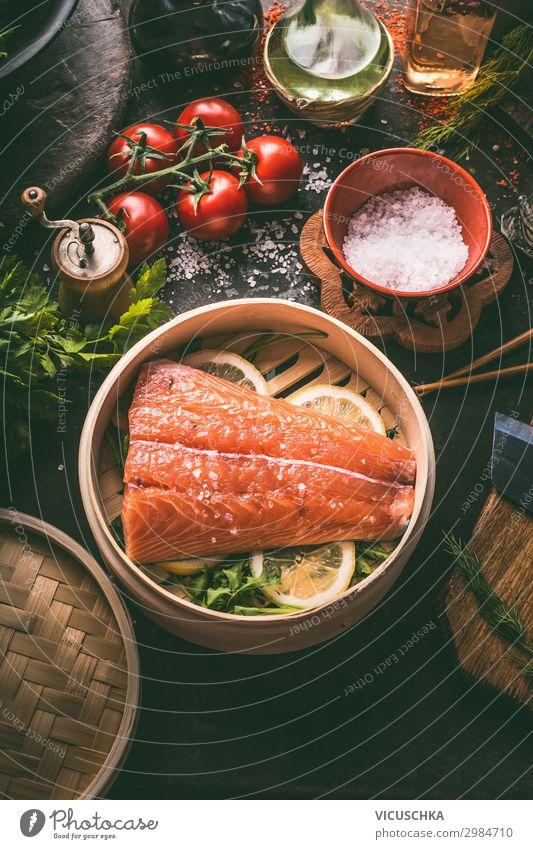 Rohes Lachsfilet im Bambusdämpfer auf dunklem, rustikalem Küchentisch mit frischen Zutaten und Werkzeugen. Gesundes Essen und Kochen. Diät-Konzept. Asiatische Küche. Zubereitung der Speisen