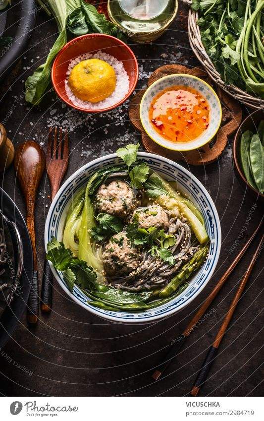 Asiatische Nudelschüssel mit grünem Gemüse, Bok Choy und Fleischbällchen auf dunklem Hintergrund mit Holzbesteck, Essstäbchen und scharfer Sauce, Ansicht von oben. Nahaufnahme. Gesundes asiatisches Essen. Konzept der asiatischen Küche