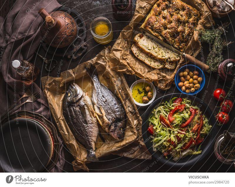 Mediterranes Mittag- oder Abendessen mit gebratenen Doradenfischen, hausgemachtem Focaccia-Brot, Olivenöl und Oliven, serviert auf einem rustikalen Tisch mit Geschirr und Küchenutensilien, Ansicht von oben.