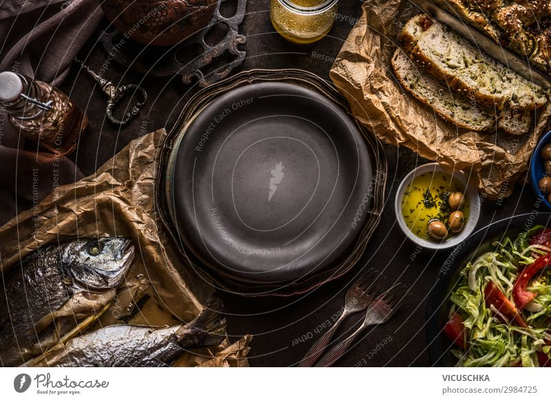 Essenshintergrund der mediterranen Küche mit Focaccia-Brot , gebratenen Doradenfischen, Salatschüssel und Olivenöl auf dunklem, rustikalem Küchentisch um den leeren Teller herum. Köstliches Konzept der mediterranen Küche.