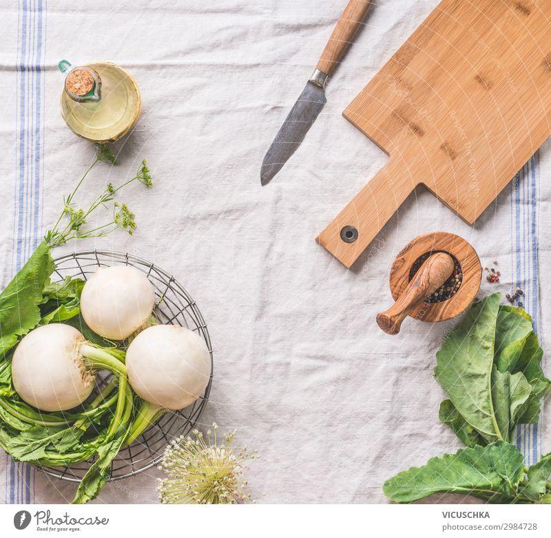 Lebensmittelhintergrund mit roher junger Rübe mit Grünzeug auf hellem Küchentisch mit Schneidebrett und Messer, Draufsicht. Gesundes vegetarisches Ess- und Kochkonzept. Kopierraum für Ihr Design