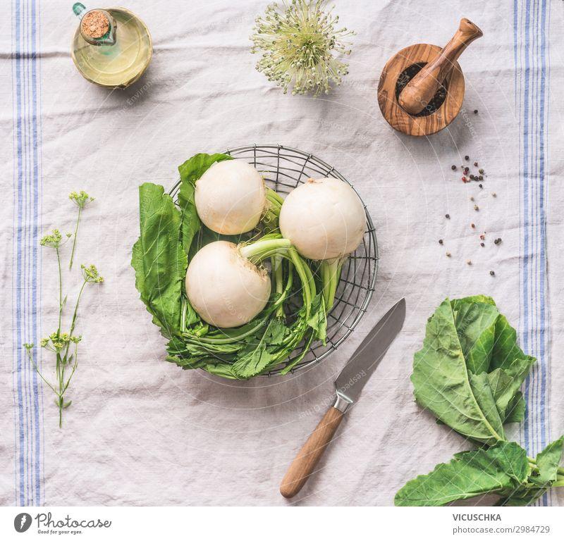 Rohe junge Rübe mit Grünzeug auf hellem Küchentisch mit Messer, Draufsicht. Konzept für gesundes vegetarisches Essen und Kochen roh Suppengrün Licht Tisch