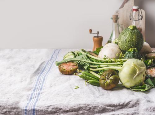 Verschiedene grüne Bio-Gemüse auf dem Küchentisch Lebensmittel Ernährung Bioprodukte Vegetarische Ernährung Diät Geschirr Stil Gesunde Ernährung Tisch weiß