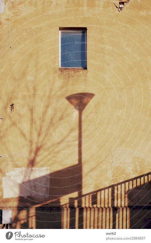 Haus mit Lampe Stadtrand Mauer Wand Fassade Fenster alt groß hoch gelb Laternenpfahl Straßenbeleuchtung Baumschatten Geländer rau Leerstand Farbfoto